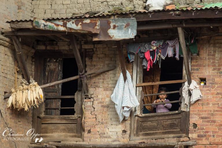 Kind in einem brüchigen Haus in Nepal