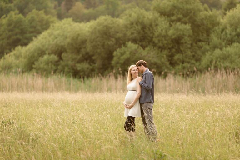 Lebendige, natürliche Schwangerschaftsfotos und Babybauchfotos draußen im Sommer, Paar steht in der Wiese
