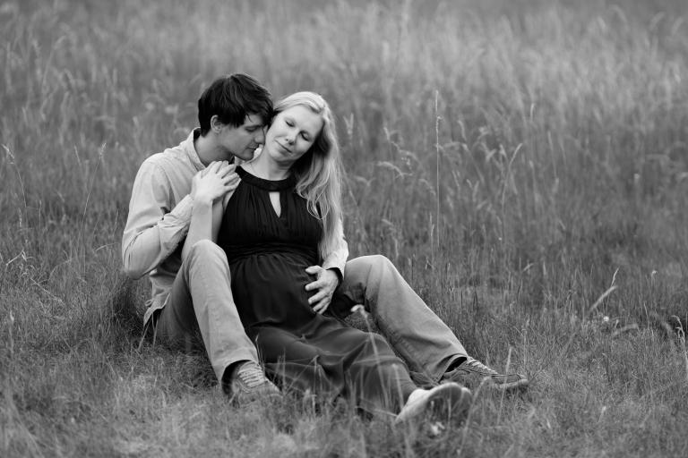 Lebendige, natürliche Schwangerschaftsfotos und Babybauchfotos draußen im Sommer, Paar sitzt in der Wiese